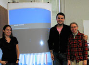 Photo of three people beside curved rear projection screen.
